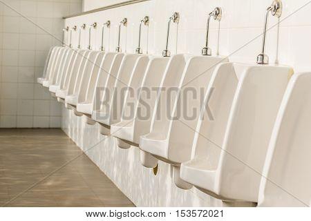 row of outdoor urinals men public toilet