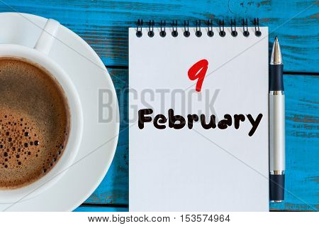 February 9th. Day 9 of month, calendar in notepad on wooden background near morning cup with coffee. Winter time. Empty space for text.
