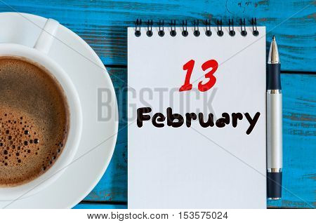 February 13th. Day 13 of month, calendar in notepad on wooden background near morning cup with coffee. Winter time. Empty space for text.