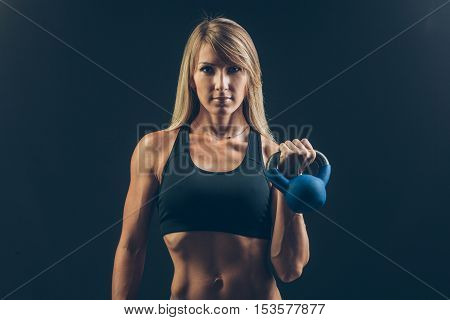 Fitness woman exercising crossfit holding kettlebell strength training biceps. Beautiful sweaty fitness instructor on blackoard background looking intense at camera. Asian Caucasian female model