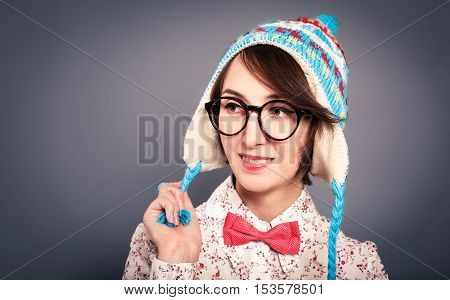 Studio Portrait of Trendy Smiling Hipster Girl in Funny Hat and Glasses. Beautiful Winter Female Teen. Gray Background. Toned Photo with Copy Space.