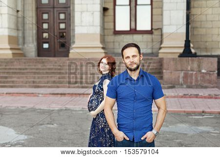 Stylish family expecting for a baby and posing on background of city street. Pregnant red hair woman with baby bump. Tender moments of parenthood.