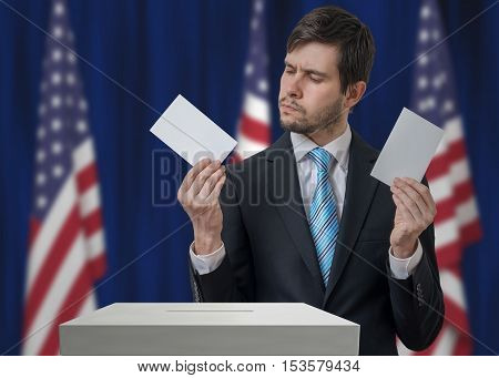 Election In Usa. Undecided Voter Holds Envelopes In Hands Above
