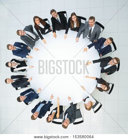 Top view of smilimg business team, sitting at a round table on w