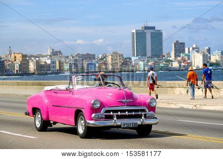 HAVANA,CUBA - OCTOBER 25,2016 : Classic american convertible car and fishermen at the famous seaside Malecon avenue in Havana