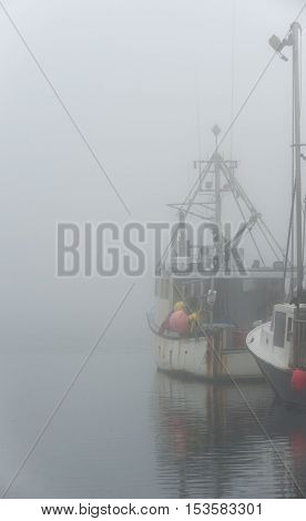 Westport Massachusetts USA - September 2 2014: Docked fishing boats sit quietly on foggy morning