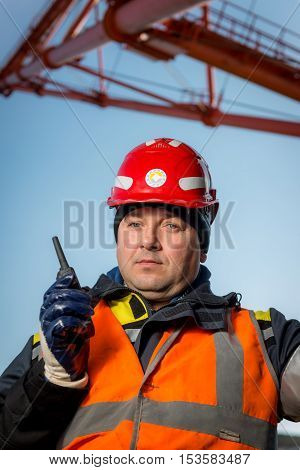 RUSSIA - OCTOBER 19: worker in an open pit with huge excavator on the background