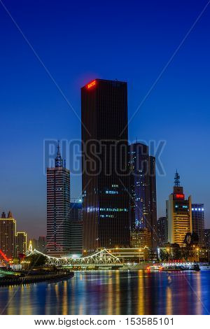 Tianjin,China - September 28,2016 : NIght scene cityscape of Tianjin city at Hai he river zone with dark blue sky background in twilight time popular landmark zone in Tianjin city China.