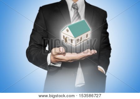 Realtor businessman with home model on hand, realtor business, home ownership, real estate concept