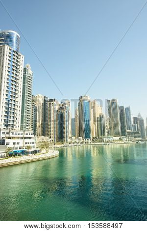 DUBAI, UAE - OCTOBER 07, 2016: Dubai Marina is a man made marina stretching over 3km of land. Surrounded by tall unique skyscrapers with apartments and restaurants, the marina is open to The Gulf.