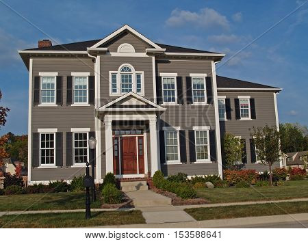 New large two-story tan home styled to look like an historic house.