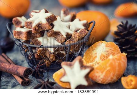 Star shape Christmas cookie on a wooden background surrounded by mandarins and traditional Xmas spices