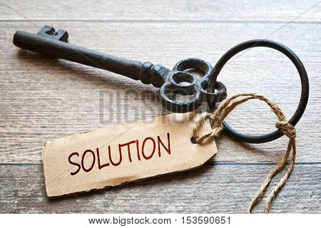 Keys to Success - Concept photo. Old key with paper label on wooden background - Solution text.