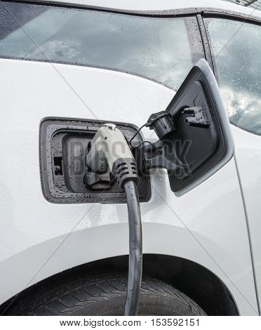 Electric vehicle charging. Charging port of electric car. Charging an electric car with the power supply plugged in.