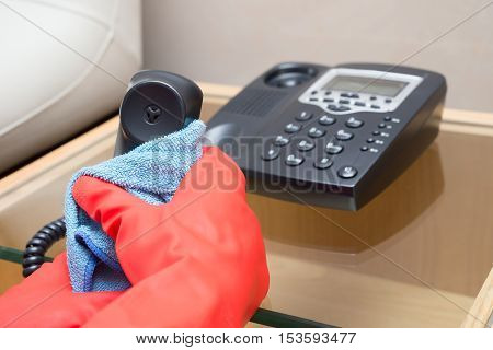 man cleaning telephone with a blue cloth