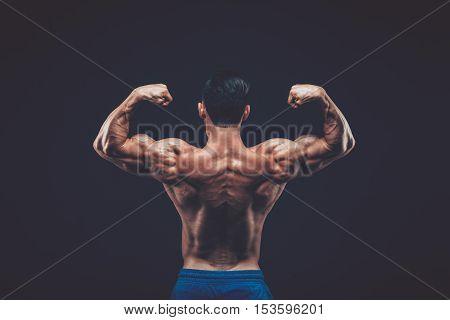 Muscular man posing in dark studio. on black background.