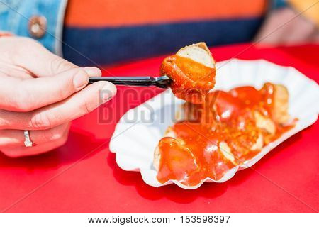 Woman Eating Currywurst in Berlin diner
