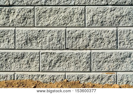 Stone wall texture. Concrete block wall of land terrace with ground on the bottom