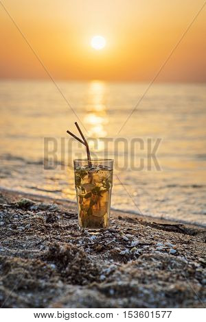 Close-up shot of glass with mojito cocktail with two straws on beach, sunset and sea in background