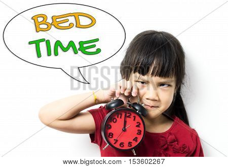 Asian girl is angry and wanting to go to bed. Girl holding a clock counting at mid night to requesting Bed Time. Sleepy tired little girl need to go bed to sleep.