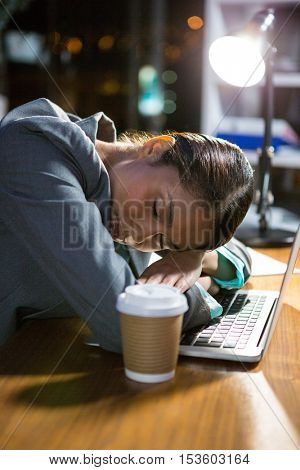 Businesswoman sleeping while working in office at night
