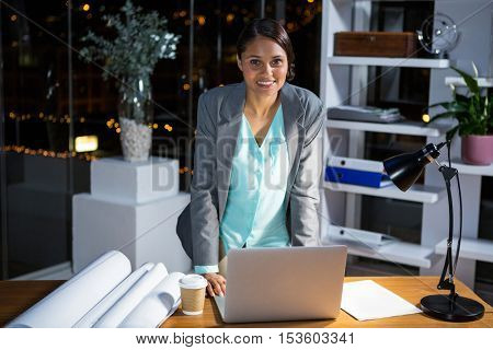 Portrait of businesswoman working on laptop in office at night