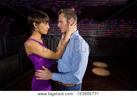 Cute couple dancing together on dance floor in bar