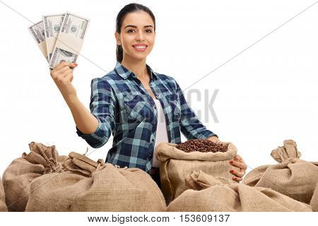 Female farmer posing with a pile of burlap sacks filled with coffee beans and money bundles isolated on white background