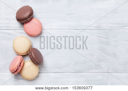 Colorful macaroons on wooden table. Sweet macarons. Top view with copy space for your text