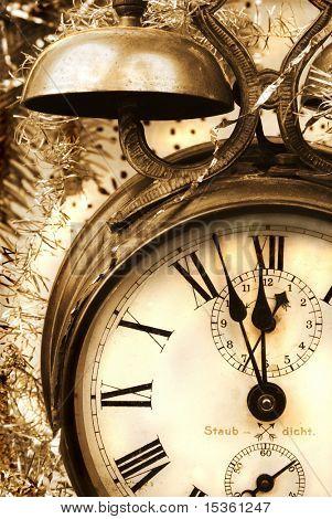 Vintage alarm-clock in sepia tone. New Year celebration