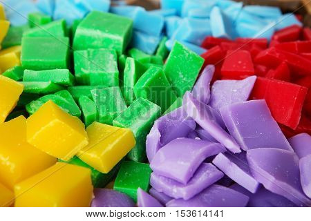 Pieces of colored wax. varicoloured pieces of beeswax to make candle as background.