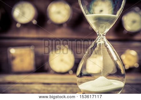 Aged hourglass with flowing sand on old wooden table