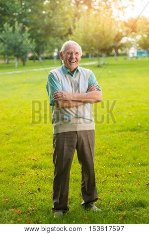 Man with crossed arms laughing. Senior male standing outdoor. Only I understand your jokes. Good mood guaranteed.