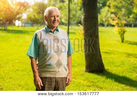 Senior man standing outdoor. Person with gray hair smiling. Realizing the passage of time. I achieved everything I wanted.