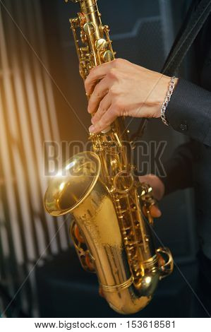 Musical instrument saxophone close-up. Hands on a musical instrument. Young guy playing jazz.