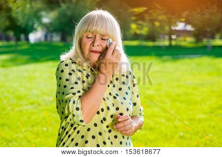 Old woman crying. Lady wiping tears with napkin. No joy in life. Feel weak and miserable.