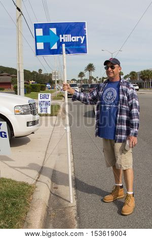 JACKSONVILLE, FLORIDA - OCTOBER 25, 2016: A Hillary Clinton supporter holding a political election sign in front of a early voting site 13 days before the general election.