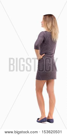 back view of standing young beautiful  woman.  girl  watching. Rear view people collection.  backside view of person.  The girl in a brown dress is standing resting his arm on the side.