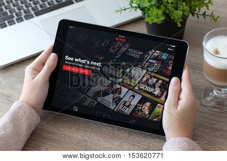Alushta Russia - October 9 2016: Woman holding a iPad Pro Space Gray with multinational entertainment company Netflix provides streaming media and video on the screen. iPad Pro 9.7 was created and developed by the Apple inc.