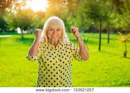 Smiling woman with raised fists. Happy senior lady. Small victories every day. Cheerful and energetic.