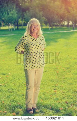 Woman with hands behind back. Smiling senior female outdoors. I like this park. Good view raises mood.