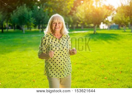 Senior woman standing and smiling. Lady on park background. Vacation has just begun. Feel the energy of summer.