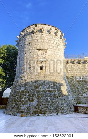 The round venetian tower of Frankopan Castle at Kamplin square in Krk Croatia - Frankopanski Kastel and plate with a winged Venetian lion the symbol of St. Mark. Part of the medieval city walls.