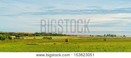 Panorama of hay bales on a farm along the ocean with the Confederation Bridge in the background (Prince Edward Island Canada)