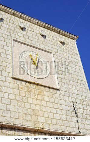 The Krk Town Council Hall clock at Vale Market place on island Krk Croatia. A rook medieval structure with a 24h clock with latin numbers and yellow pointers.