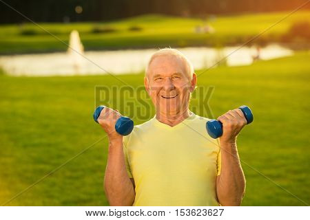 Senior man with dumbbells smiling. Old guy on nature background. Lift weights to become stronger. Sport is my life.
