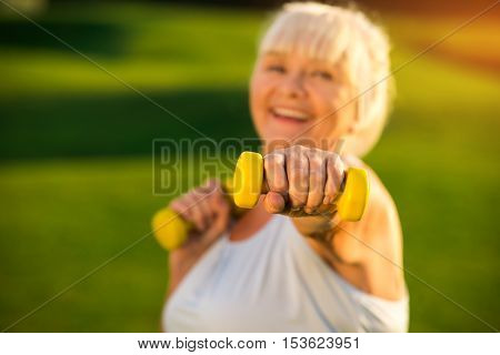 Senior woman holding dumbbell. Elderly lady with smiling face. I train to become healthier. Fight with the laziness.