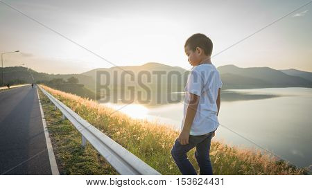 scared and alone, young homeless Asian child who is at high risk of bing bullied and abused