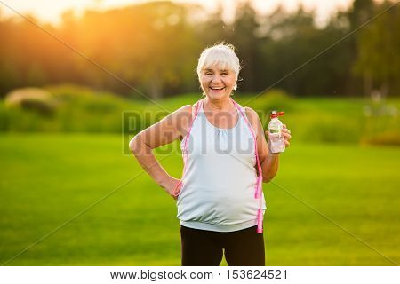 Woman with water bottle smiling. Senior lady outdoors. New program of aerobic trainings. Start your fitness journey today.