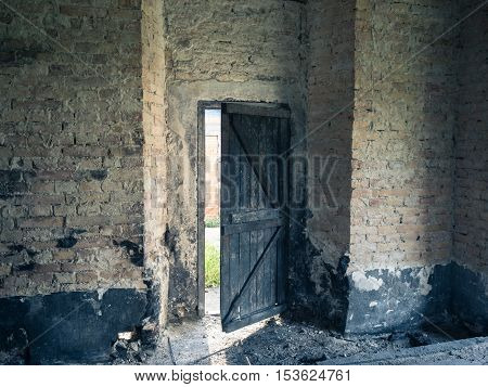 An old building ruined by the time. The door to the ruined building, HDR photo the charred old door against a brick wall